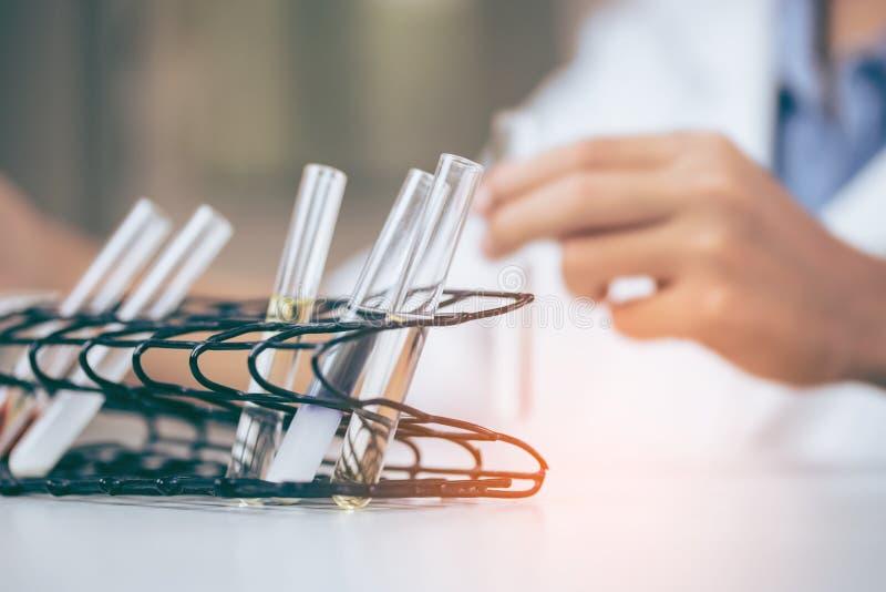 O cientista asiático novo é determinadas atividades na ciência experimental como produtos químicos ou os dados de mistura da entr imagens de stock royalty free
