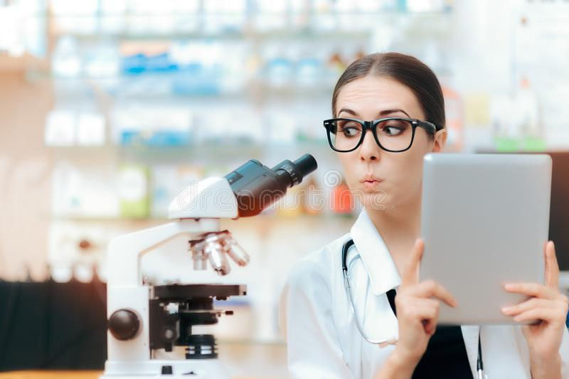 O cientista com a tabuleta do microscópio e do PC que faz a pesquisa estuda imagem de stock royalty free