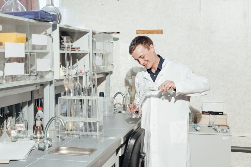O cientista conduz experiências químicas no laboratório imagens de stock