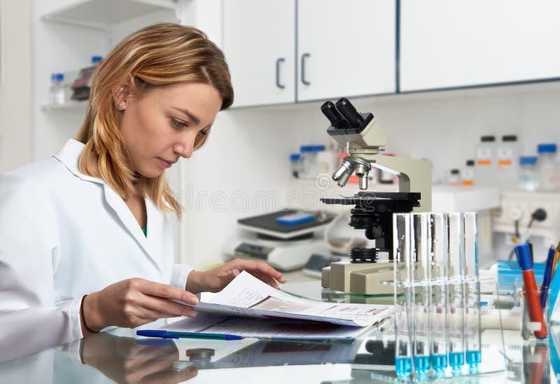 O cientista fêmea europeu novo verifica seu jornal do laboratório imagem de stock