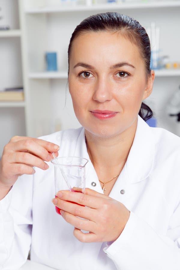 O cientista fêmea novo no laboratório, fazendo experimenta no laboratório fotografia de stock