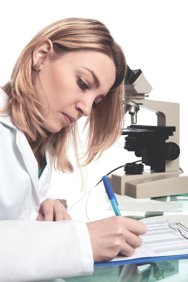 O cientista fêmea novo ou a tecnologia escrevem o relatório científico imagem de stock