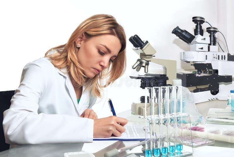 O cientista fêmea novo ou a tecnologia escrevem para baixo o relatório de progresso imagens de stock