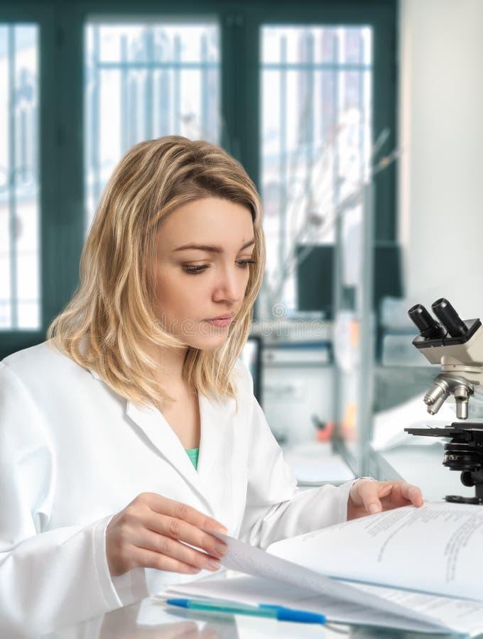 O cientista fêmea novo trabalha no laboratório moderno imagens de stock