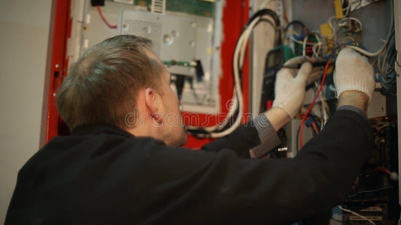 O cientista faz medidas elétricas no painel de comando video estoque