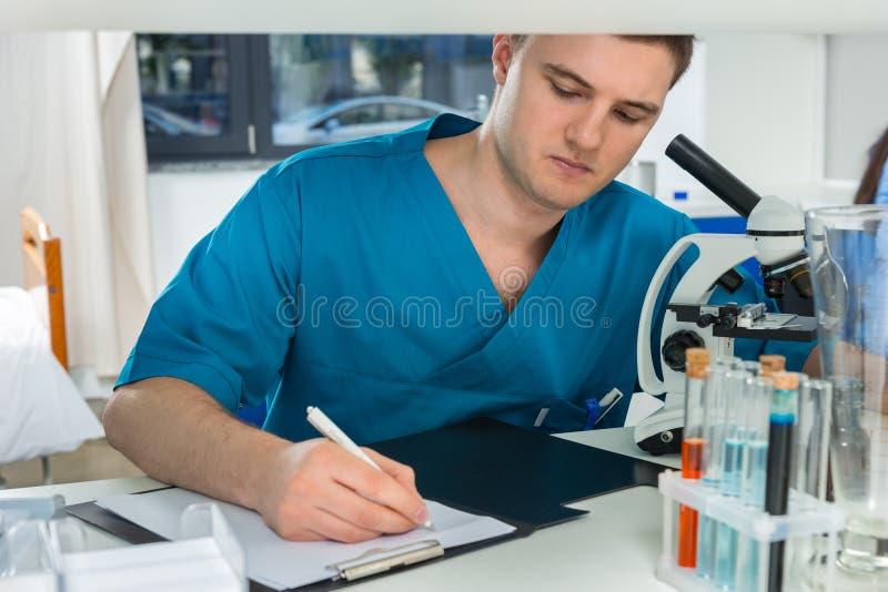 O cientista masculino novo no uniforme está escrevendo para baixo notas de seu res fotografia de stock