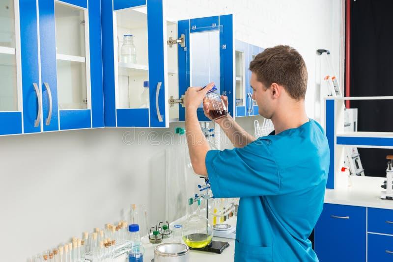 O cientista masculino novo no uniforme está olhando a garrafa com chemi imagens de stock royalty free