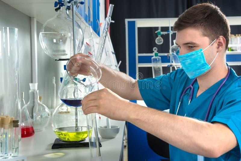 O cientista masculino novo no uniforme que veste uma máscara está guardando o teste g imagens de stock royalty free