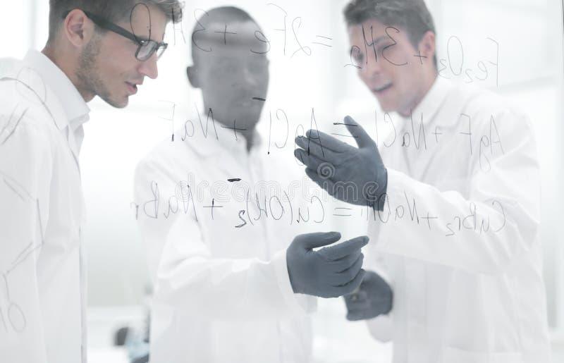 O cientista novo faz anotações em uma placa de vidro fotografia de stock royalty free