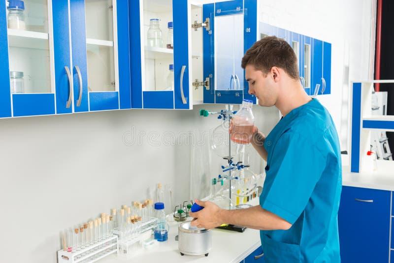 O cientista novo no uniforme está cheirando uma garrafa com produto químico s foto de stock royalty free