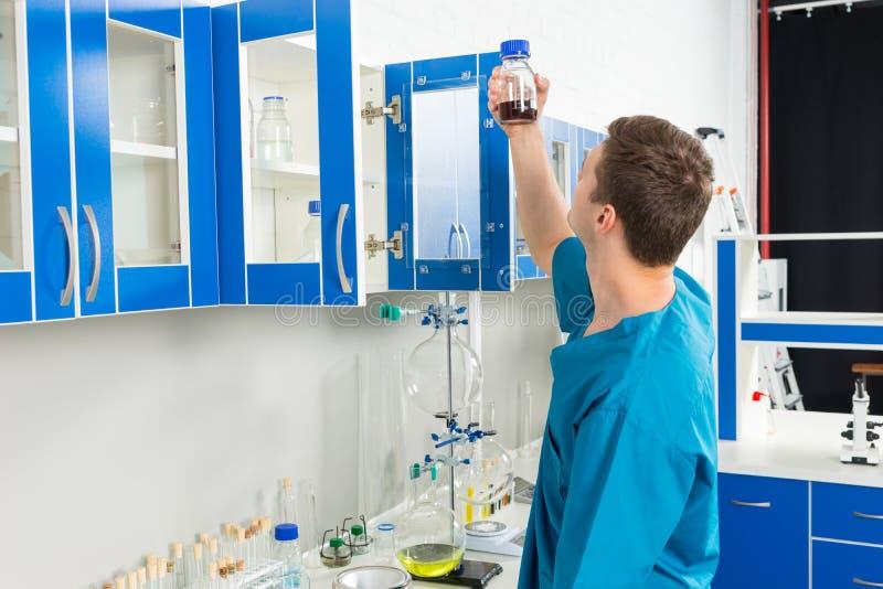 O cientista novo no uniforme está olhando a garrafa com produto químico s imagem de stock