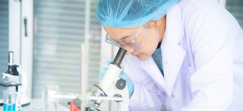 O cientista, o pesquisador, o técnico, ou o estudante asiático da mulher conduziram a pesquisa ou a experiência usando o microscó imagem de stock
