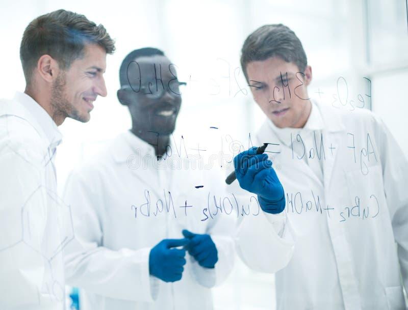 O cientista prometedor faz anotações na placa fotografia de stock