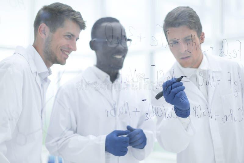 O cientista prometedor faz anota??es na placa fotografia de stock
