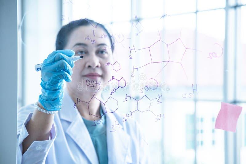 O cientista químico da mulher asiática escreve o formular na placa de vidro foto de stock royalty free