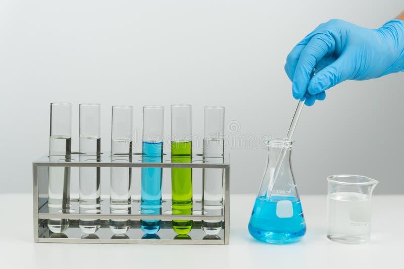 o cientista que guarda a haste de agitação de vidro foto de stock