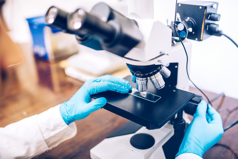 O cientista que usa o microscópio para o teste da química prova e sonda equipamento ou ferramentas médicas e científicas do detal foto de stock