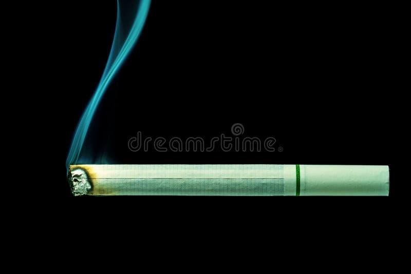 O cigarro branco é queimadura no fundo preto imagens de stock royalty free