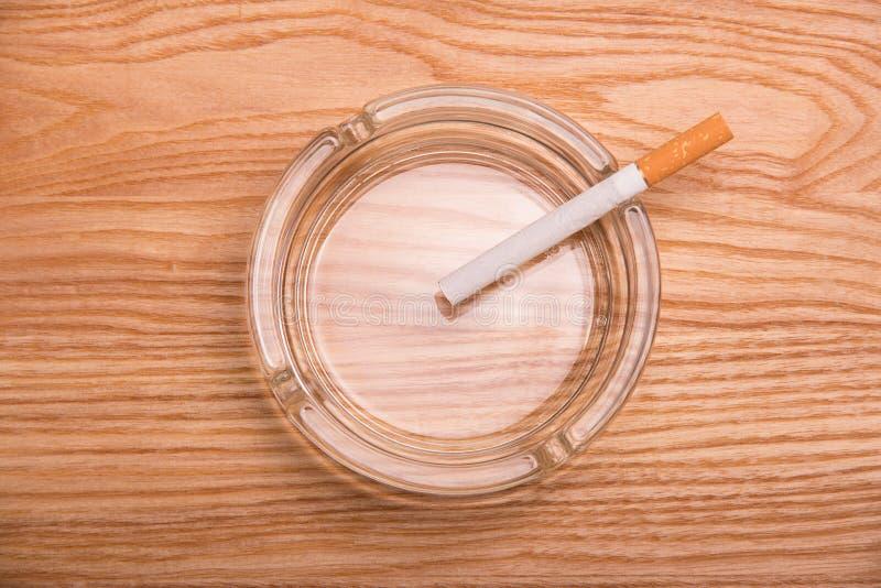 O cigarro com filtro encontra-se em um cinzeiro, na superfície de madeira imagens de stock royalty free