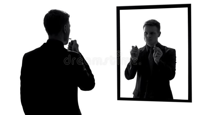 O cigarro da iluminação do homem, pedir da voz da consciência parou fumar, reflexão de espelho imagens de stock