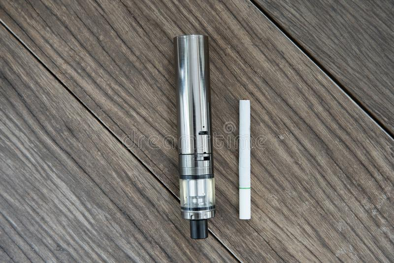 O cigarro eletrônico com os cigarros regulares foto de stock