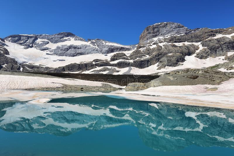 O cilindro de Monte Perdido Peak e de Marbore de Marbore congelou o lago no parque nacional de Ordesa, Espanha fotografia de stock