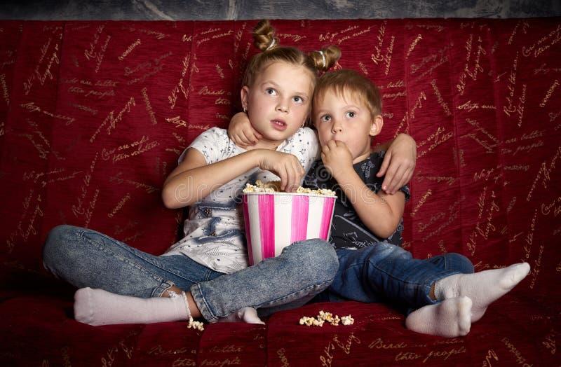 O cinema das crianças: Uma menina e um menino olham um filme em casa em um sofá vermelho grande na obscuridade e comem a pipoca imagem de stock