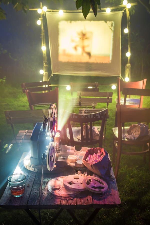 O cinema retro com bebidas e a pipoca no verão jardinam fotografia de stock royalty free