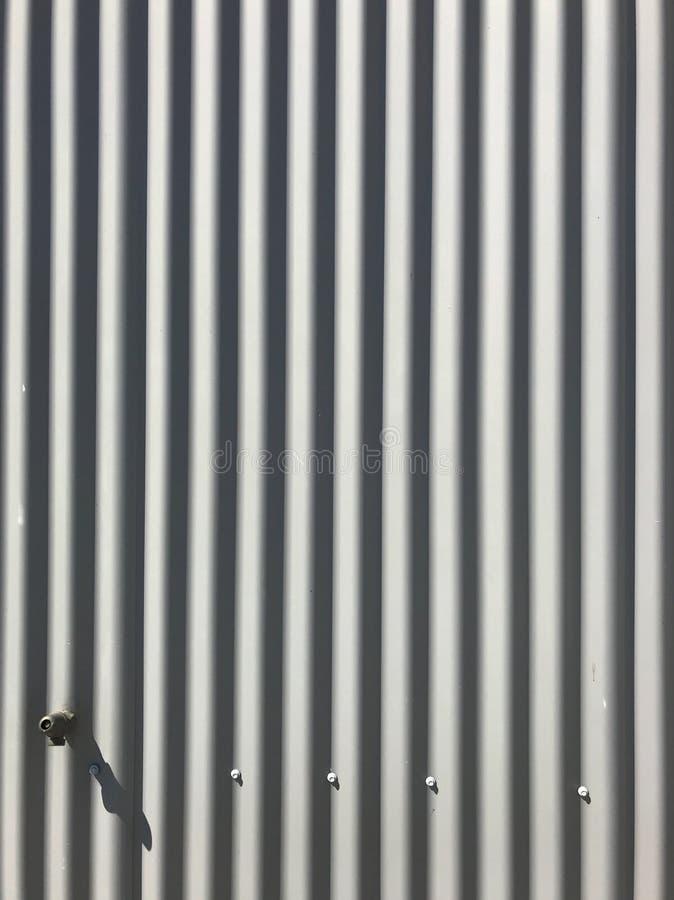 O cinza branco pintou o teste padrão metálico da textura da cerca da placa da folha do zinco ondulado no fundo da superfície da p imagens de stock