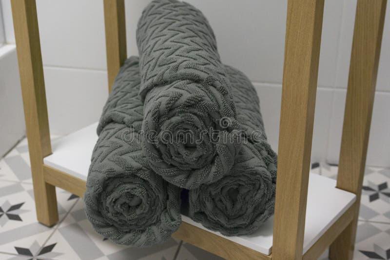 O cinza dobrou belamente toalhas em uma prateleira branca foto de stock