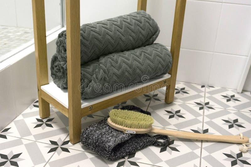 O cinza dobrou belamente toalhas em uma prateleira branca com uma escova e uma toalha de rosto da massagem imagem de stock