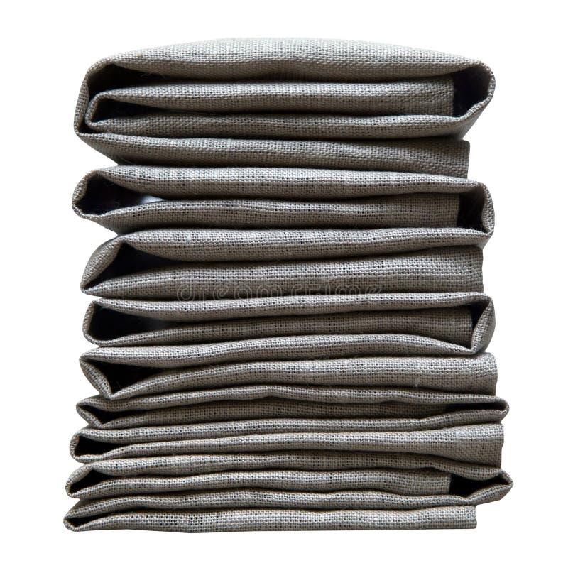 O cinza dos guardanapo dobrou a pilha isolada no fundo branco imagem de stock