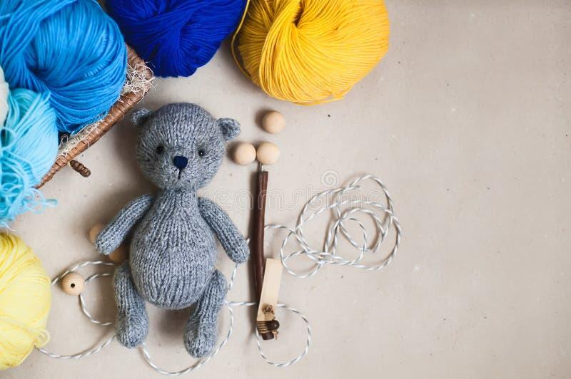 O cinza fez malha o urso e acessórios de confecção de malhas no fundo do papel de embalagem Brinquedo feito malha imagem de stock royalty free