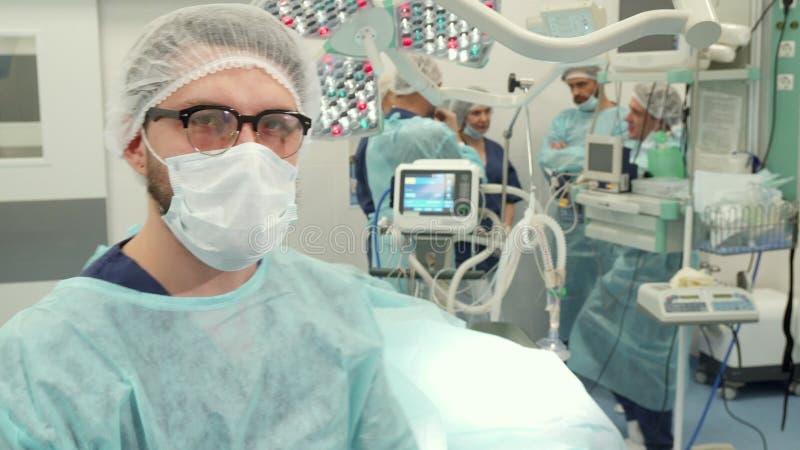 O cirurgião inclina-se na cirurgia imagens de stock
