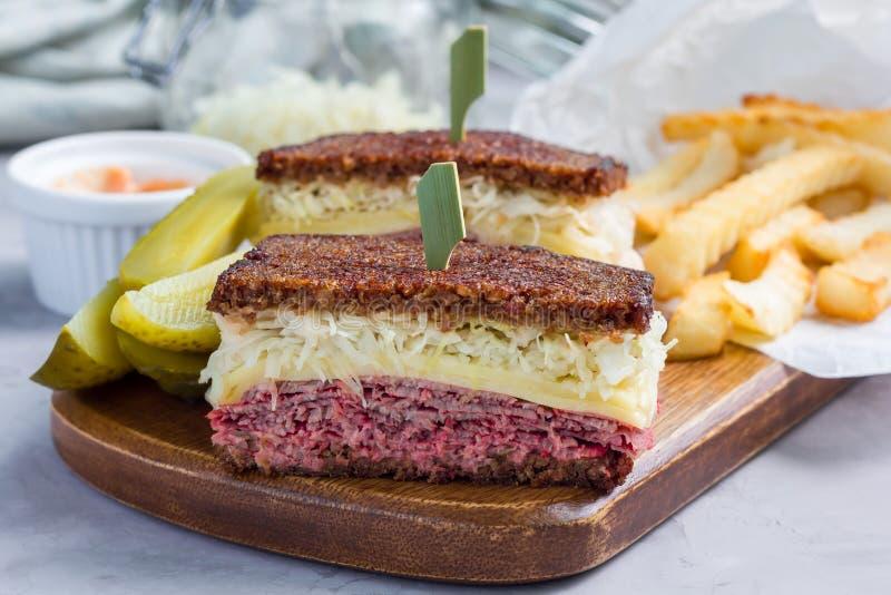 O clássico reuben o sanduíche, servido com salmoura de aneto, as microplaquetas de batata, horizontais imagem de stock royalty free