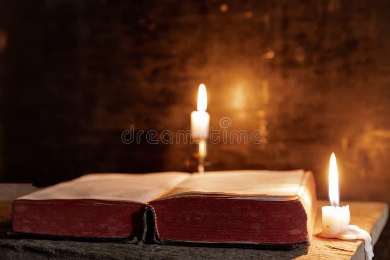 O claro iluminando a B?blia ? somente da vela Aperfei?oe para a religi?o, easter fotos de stock royalty free