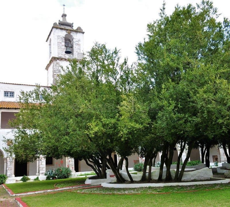 O claustro, o jardim e a torre de igreja imagens de stock