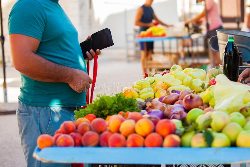O cliente abre uma carteira com dinheiro para pagar as frutas fotografia de stock