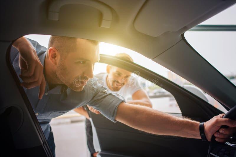 O cliente considerável e seguro está e inclina-se ao carro Guarda o volante com uma mão O indivíduo é atento a fotos de stock