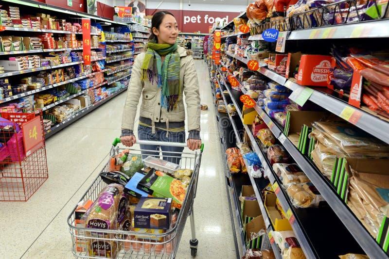 O cliente consulta o corredor do supermercado fotos de stock royalty free