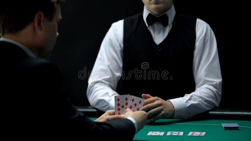 O cliente do homem de negócios do casino obtém a mão má do crouoier da casa, pôquer jogando foto de stock royalty free
