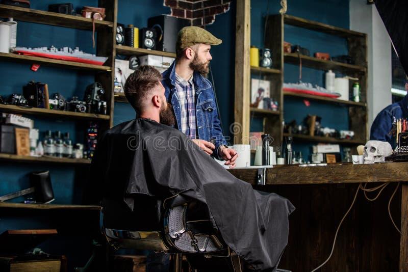 O cliente do moderno obteve o corte de cabelo novo Aparagem terminada barbeiro Barbeiro com o homem farpado que olha o espelho, b imagens de stock royalty free