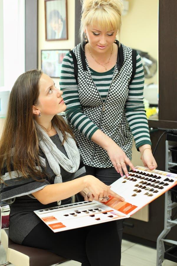 O cliente e o cabeleireiro olham o catálogo de cores do cabelo imagem de stock royalty free