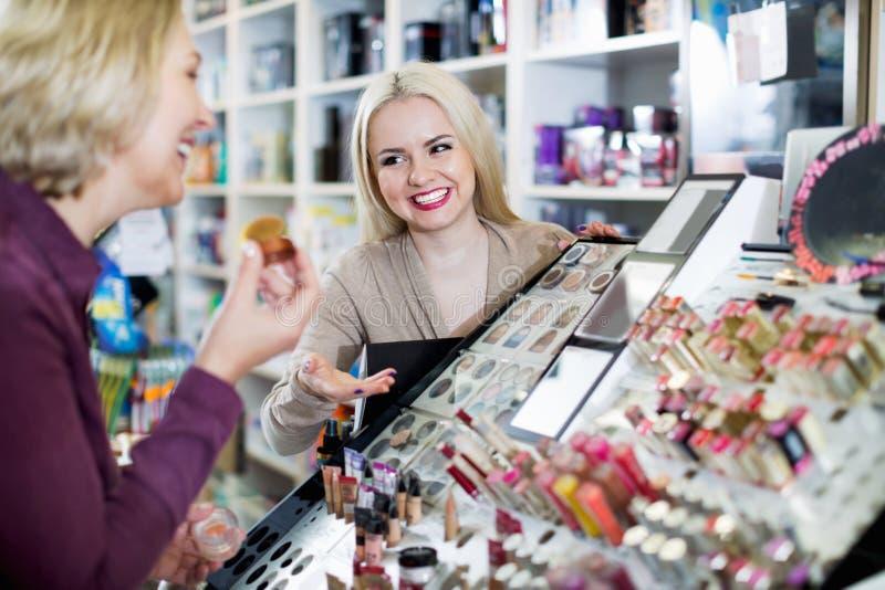 O cliente encantador positivo da mulher escolhe cosméticos imagens de stock royalty free