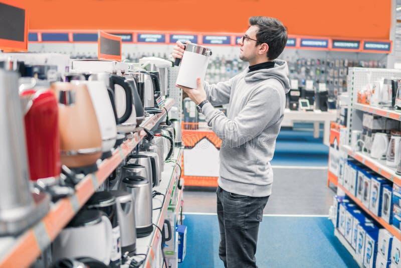 O cliente escolhe uma chaleira na alameda do supermercado imagem de stock