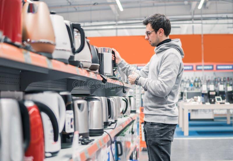 O cliente escolhe uma chaleira na alameda do supermercado imagem de stock royalty free