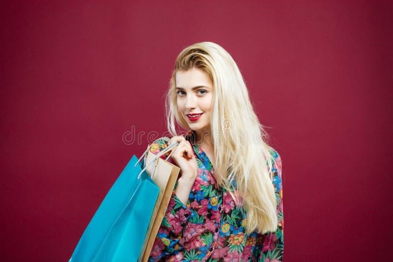O cliente fêmea louro na camisa colorida está guardando sacos de compras no estúdio Menina feliz com cabelo de Lond e sorriso enc foto de stock royalty free