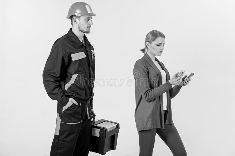 O cliente ilude o reparador, construtor, mecânico O reparador, construtor quer o salário fotos de stock