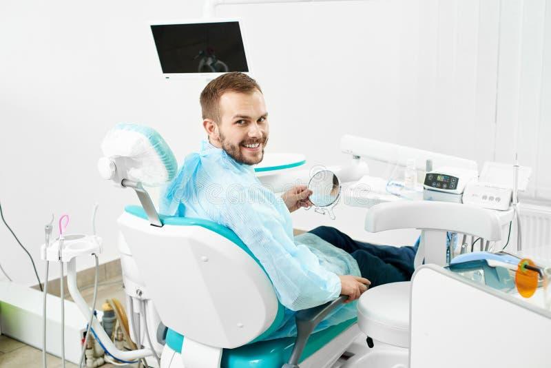 O cliente masculino novo está sorrindo à câmera ao verificar seus dentes no espelho em um armário branco moderno do dentista imagem de stock