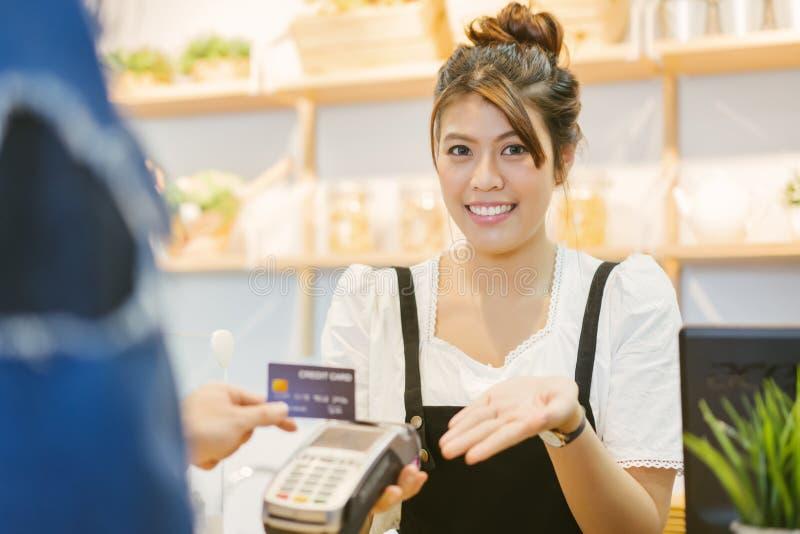 O cliente no café está pagando através do cartão de crédito ao assistente de loja imagens de stock royalty free